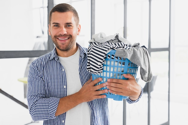 Front view man holding basket with clothes