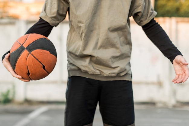 Front view man holding a basketball