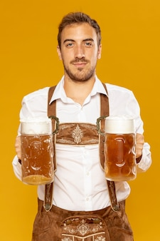Front view of man holding beer pints