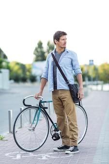 Вид спереди мужчина держит велосипед на открытом воздухе
