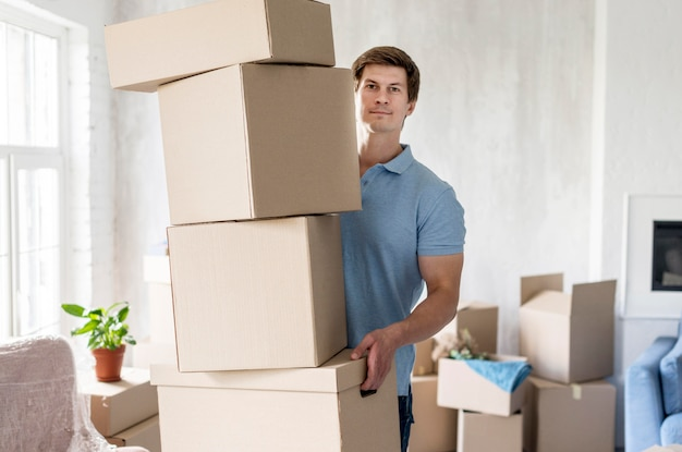 Front view of man holding boxes for moving out