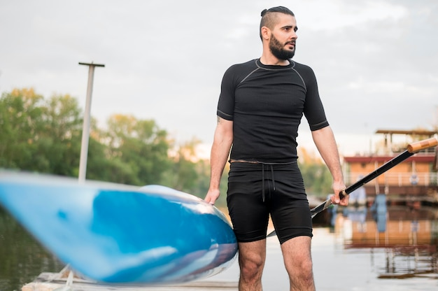 Front view man holding canoe and oar
