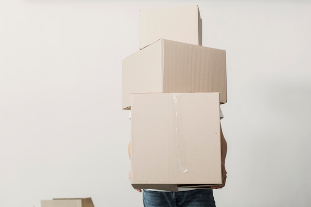 Front view man holding carton boxes