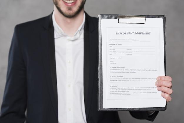 Vista frontale del contratto della tenuta dell'uomo per il nuovo lavoro