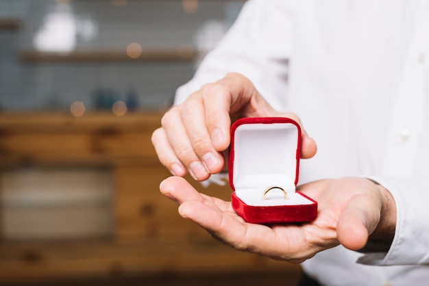 Front view of man holding engagement ring