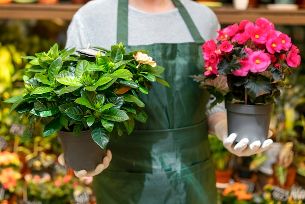 Front view man holding flowerpots with flowers