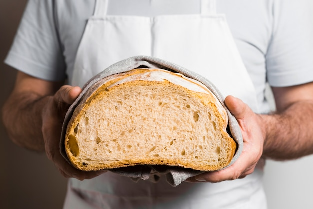 Front view man holding half of bread