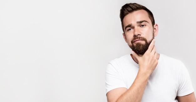 Uomo di vista frontale che tiene la sua barba con lo spazio della copia