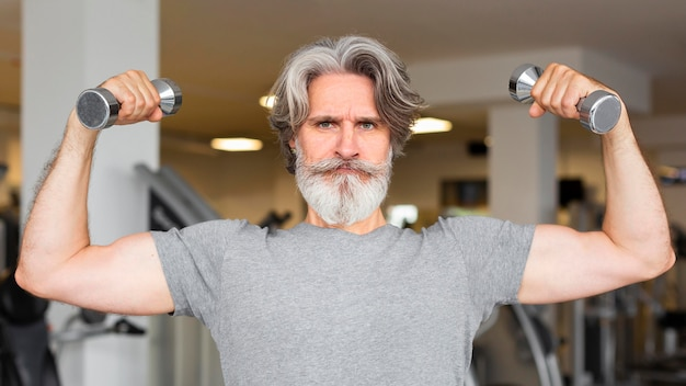 Front view man holding metal dumbbells