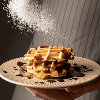 Front view of man holding plate of waffles and coating them with powdered sugar