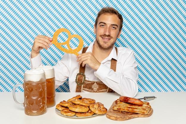 Front view of man holding pretzel