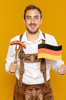 Front view of man holding sausage and flag