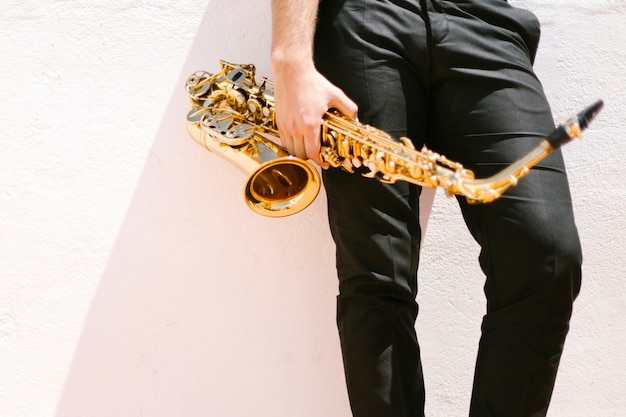 Front view of man holding saxophone