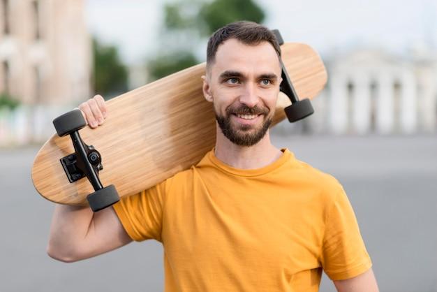 Uomo di vista frontale che tiene uno skateboard all'aperto
