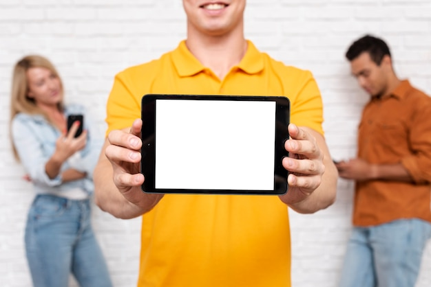 Front view man holding a tablet with mock-up