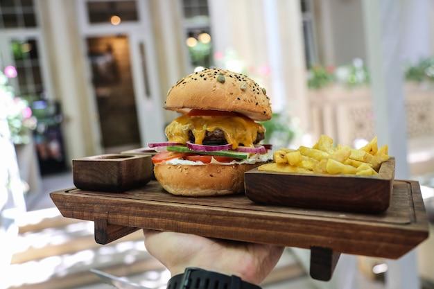 Vista frontale un uomo che tiene un vassoio di hamburger di carne con cipolle rosse e patatine fritte con salse