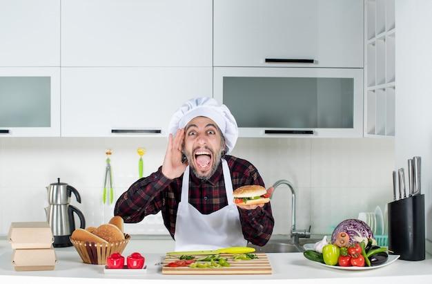台所のテーブルの後ろに立っているハンバーガーを持ち上げる正面図の男