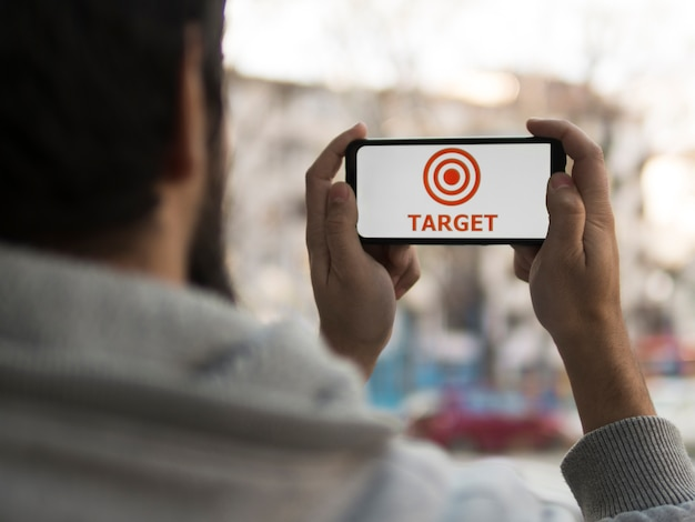 Front view of man holding up smartphone with target
