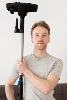 Front view man holding vacuum cleaner