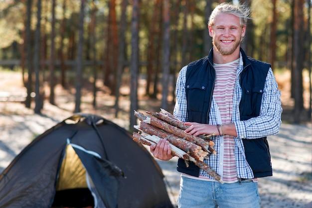 Вид спереди мужчина держит дрова для огня