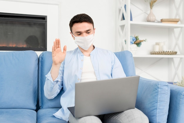 Front view of man at home with medical mask working on laptop