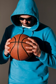 Front view of man in hoodie and sunglasses holding basketball