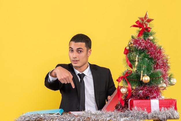 크리스마스 트리와 선물 아래로 손가락으로 가리키는 문서를 들고 테이블에 앉아 정장에 전면보기 남자