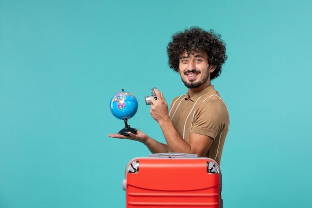 青に小さな地球儀とカメラを保持している休暇中の正面男