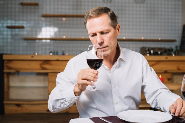 Front view of man inspecting glass of wine