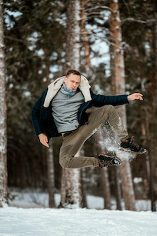 Front view of man jumping outdoors in nature during winter