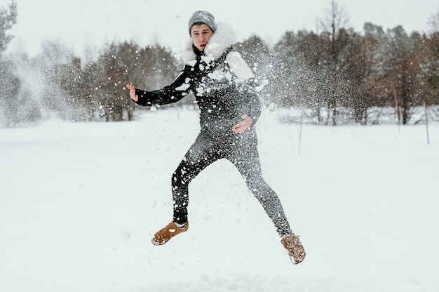 Front view of man jumping outdoors in winter