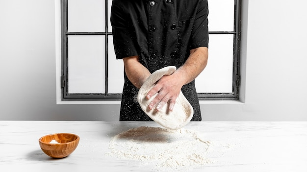 Front view man kneading pizza dough