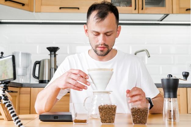 Uomo di vista frontale che produce caffè