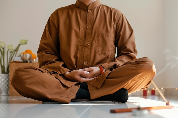 Front view of man meditating with incense