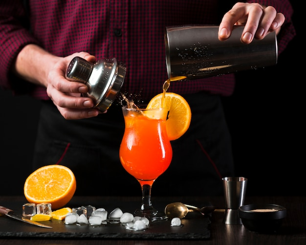 Front view of man mixing cocktail