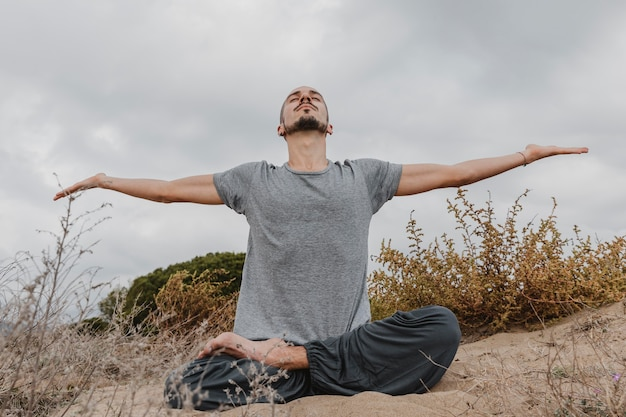 Front view of man outdoors doing yoga