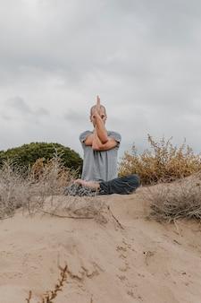 Vista frontale dell'uomo fuori meditando mentre si fa yoga