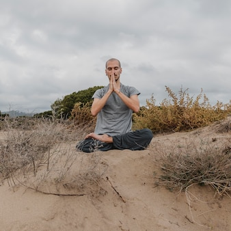 Front view of man outside relaxing while doing yoga
