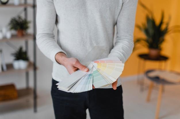 Vista frontale dell'uomo che intende ridipingere la casa usando la tavolozza della vernice