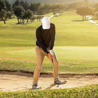 Vista frontale dell'uomo che gioca a golf con il club