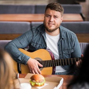 テーブルでギターを弾く正面図の男