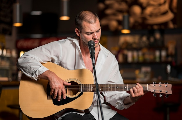 Front view man playing guitar in a bar