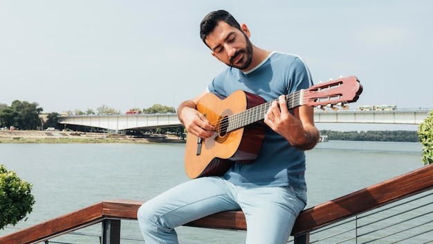 Front view of man playing the guitar