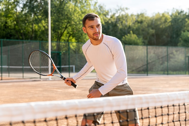 Front view man playing tennis