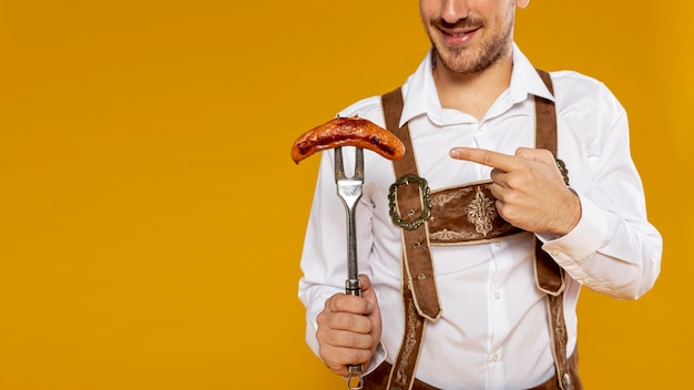 Front view of man pointing at sausage