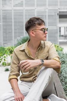 Vista frontale dell'uomo in posa elegante con una tazza di caffè e occhiali da sole