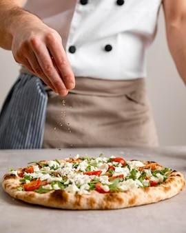Вид спереди мужчина поливает запеченную пиццу зеленью