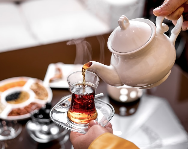Front view a man pours tea in a glass of armudu from a teapot of tea and holds a glass