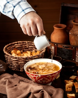 Front view a man pours vinegar into hash a traditional azerbaijani dish in a kyasa plate with crackers