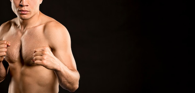 Front view of man practicing boxing stance with copy space